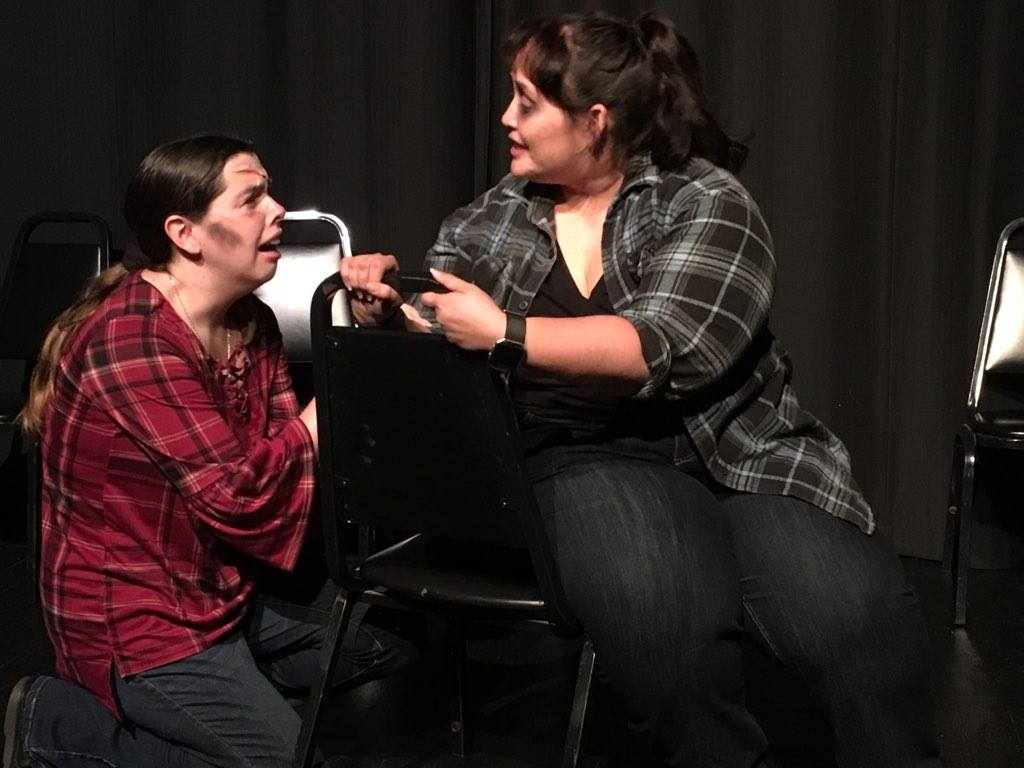 Dominica kneels on the floor with a scar on her forehead and is clearly distressed, while Alissa sits on a backwards chair and tries to comfort her.